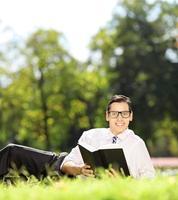 junger Mann, der auf Gras mit Buch liegt