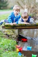 zwei kleine Brüder, die mit Papierbooten an einem Fluss spielen