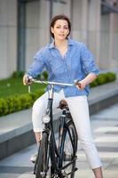 hübsches Mädchen, das auf einem Fahrrad an der Straße sitzt foto