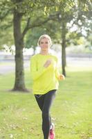 aktive glückliche Blondine, die in Richtung Kamera joggt