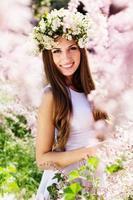 schönes Mädchen auf der Natur im Kranz der Blumen