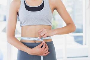Mittelteil einer Frau, die Taille im Fitnessstudio misst foto
