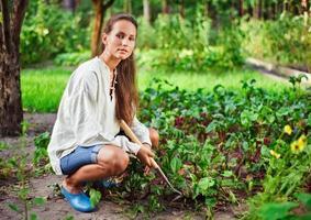 junge Frau mit Hacke, die im Gartenbett arbeitet