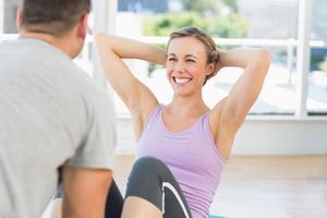 Trainer, der fitte Frau dabei unterstützt, setzt sich auf