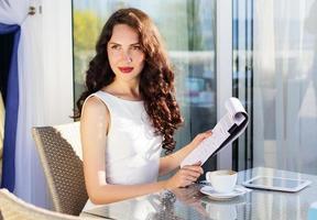 Mädchen, das Zeit in einem Café mit digitalem Tablet verbringt foto