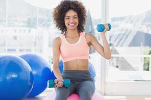 Frau, die mit Hanteln auf Fitnessball im Fitnessstudio trainiert
