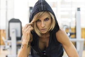 Fitnessfrau in der Sportbekleidung, die Kamera betrachtet