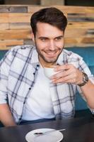 junger Mann, der eine Tasse Kaffee trinkt foto