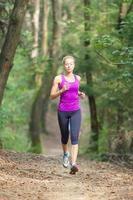 hübsche junge Läuferin im Wald. foto