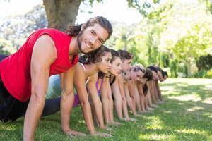 Fitness-Gruppe Planking im Park foto
