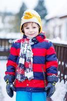 Porträt des kleinen Kindes in der bunten Kleidung im Winter, im Freien foto