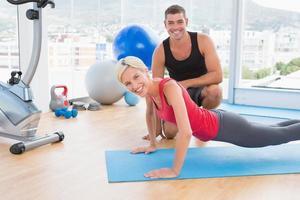 blonde Frau, die mit ihrem Trainer auf Übungsmatte arbeitet
