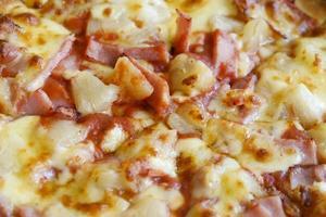 köstliche hawaiianische Pizza im rustikalen Stil mit frischen Ananas foto