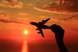 Schattenbild der Hand, die Flugzeugminiatur mit Sonnenunterganghintergrund hält foto