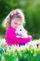 schönes kleines Mädchen, das mit einem Kaninchen spielt foto