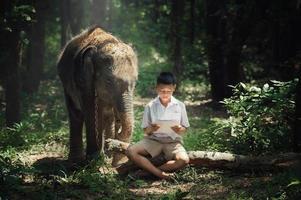 Junge, der Buch mit Elefant an der Elefantendorfschule in Thailand liest.