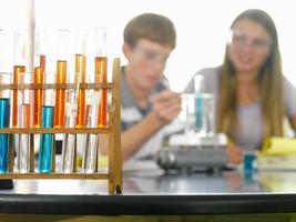 Studenten (12-14) mit Chemieexperiment konzentrieren sich auf Becher foto