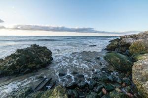 Wellen, die über Felsen im Sonnenuntergang zerquetschen