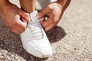 Mann, der seine Schuhe bindet foto