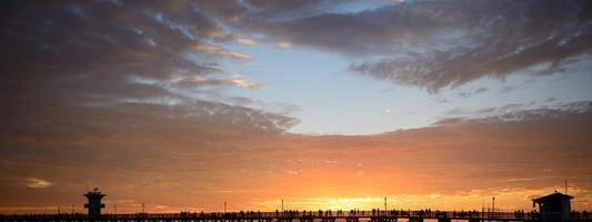 Leute, die Sonnenuntergang vom Pier Ende des Sommers beobachten foto