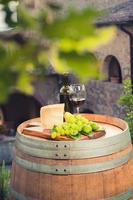 Rotwein, Pecorino-Käse, Trauben, Flasche und Glas auf Fass foto