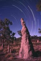 Startlauf mit Termitenhügel, der auf Sterne im australischen Outback zeigt foto