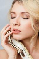 schönes Mädchen hält eine Python, die sich um ihren Körper wickelt