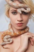 schönes Mädchen und die Schlange Boa Constrictors, die sich umhüllt foto