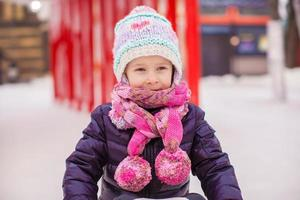 entzückendes kleines glückliches Mädchen, das auf der Eisbahn Schlittschuh läuft