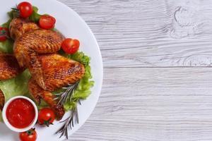 gebratene Hühnerflügel mit Sauce und Gemüse Draufsicht