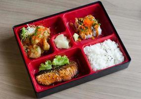 Bento Box mit Brötchen und Lachs foto