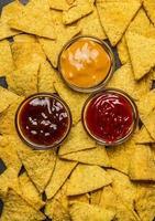 Maistortillachips Hintergrund mit verschiedenen Dips, Draufsicht, foto