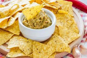 Guacamole-Sauce in weißer Schüssel, Nacho-Chips auf Holzbrett