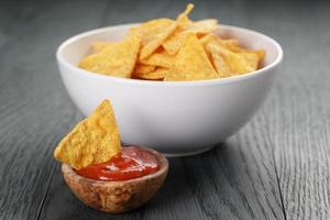 Tortillachips in weißer Schüssel mit Tomatensauce auf Tisch foto