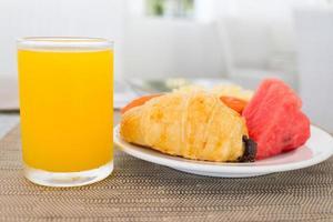 Frühstück mit Orangensaft, Croissant und Obst