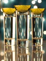 Nahaufnahme von Schüssen Glas und Limetten mit Bokeh-Hintergrund
