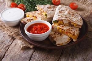Quesadilla Scheiben auf einem Teller und Saucen Nahaufnahme. horizontal foto