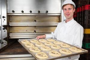 Bäcker in der Bäckerei mit Backplatte voller Brezeln foto