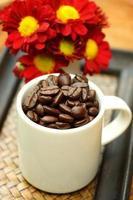 Kaffeebohne in Tasse auf Bambusschale. foto