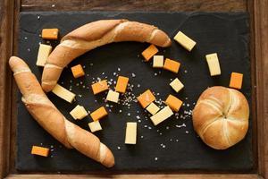 gelber und weißer Cheddar-Käse auf einem schwarzen Hintergrund