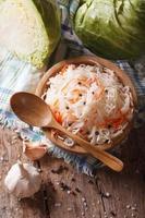 Sauerkraut und Karotten in einer vertikalen Draufsicht der hölzernen Platte foto