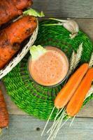 Karottensaft auf Holzhintergrund foto