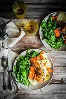 Huhn mit Kartoffeln und Rucola-Salat auf rustikalem Hintergrund foto