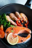 frisches Lachssteak in einer Pfanne gegrillte Garnelen und Gemüse foto