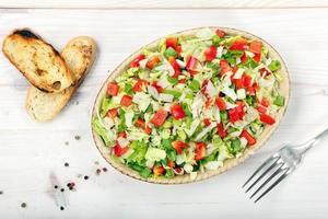 frischer Salat mit Paprika auf Holzhintergrund