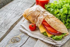 Sommersandwich mit Schinken, Käse, Salat und Tomaten, Zwiebeln, Saft foto