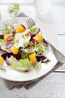 Rüben und Orangen in Salat auf Teller foto