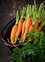 frische Karotten auf einem hölzernen Hintergrund