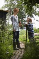 Mutter und Sohn mit Spaten im Garten