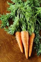 reife organische Karotten mit grünen Blättern auf einem hölzernen Hintergrund foto